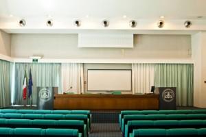l'aula magna del collegio, vista dalla platea: le poltrone verdi e il tavolo di legno dei relatori; ai lati due podi grigi con il logo del Collegio